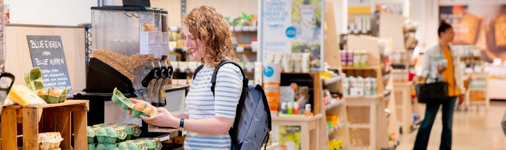 beeld vrouw supermarkt met eieren