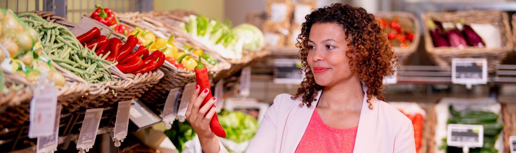 beeld vrouw bekijkt paprika