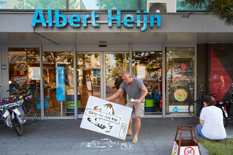 Beeld: krijtgraffiti op de stoep van Albert Heijn met de tekst Skip de AH kip