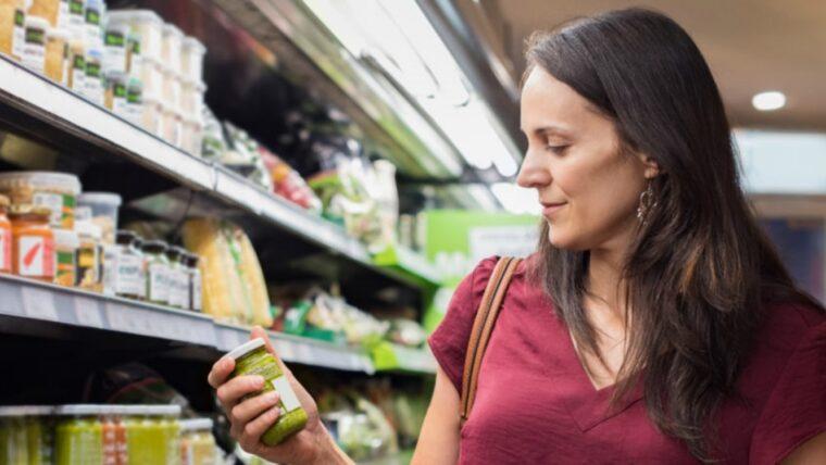 Beeld: vrouw bekijkt product uit het supermarktschap